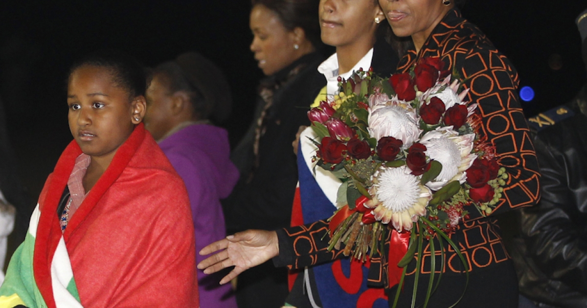 US first lady Michelle Obama holds a bouquet of flowers as daughters Malia and Sasha, are draped in blankets given to them upon landing in Pretoria en route to Johannesburg, South Africa, as they begin their week long trip to Africa on June 20, 2011.</p>