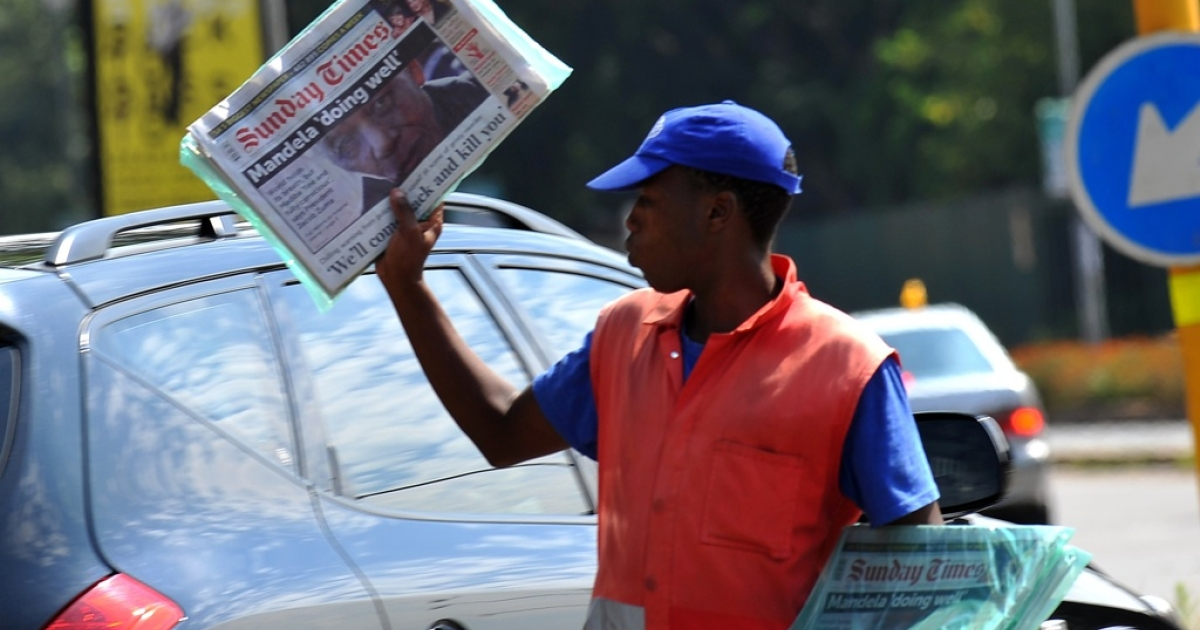 A newspaper street vendor holds up the day's edition of the South African 'Sunday Times'  on February 26, 2012, in Johannesburg.</p>