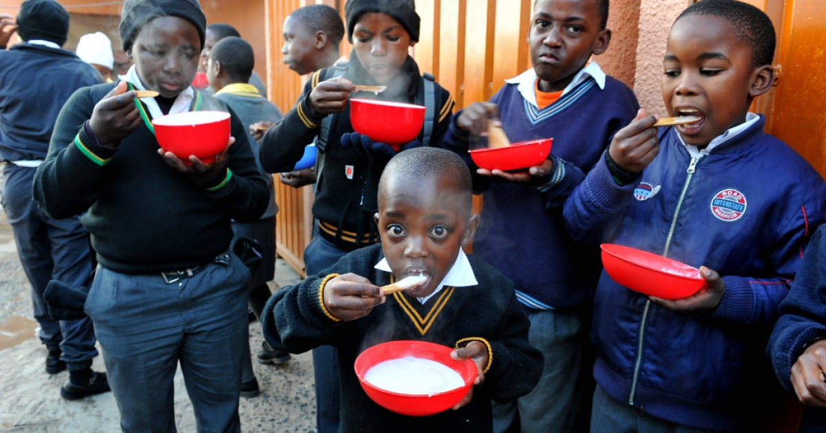 In this picture taken on May 17, 2012 some of the 100 children who have lost parents to AIDS in Alexandra township in the north of Johannesburg enjoy a bowl of piping hot corn meal porridge given to them by Mama Portia.</p>