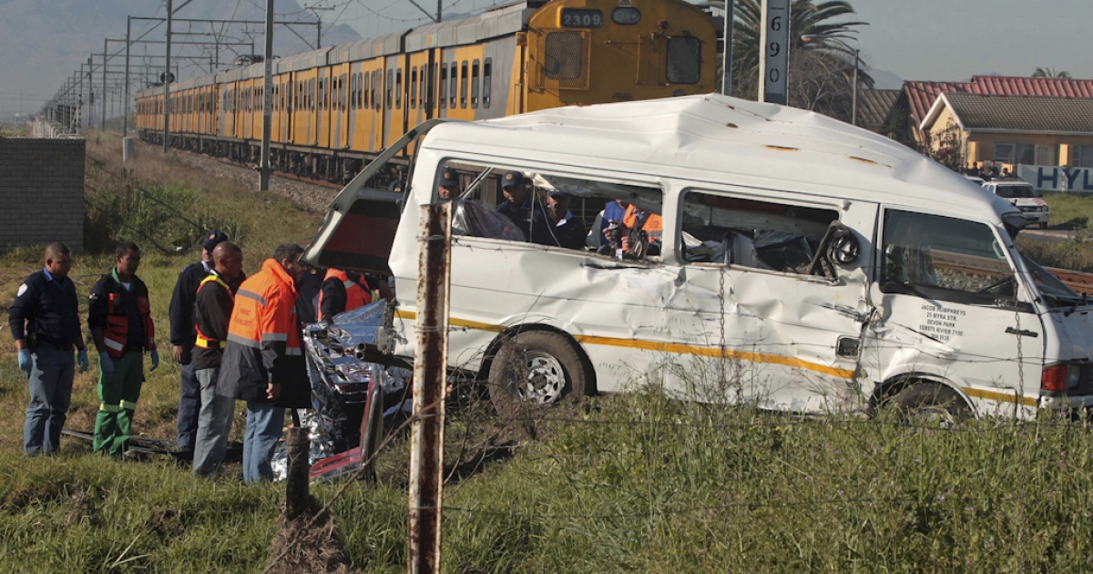 Rescuers stand at the scene of a fatal crash between a minibus taxi, carrying children to school, and a commuter train on August 25, 2010 on the outskirt of Cape Town. Road accident deaths are twice as high in South Africa as the global average.</p>