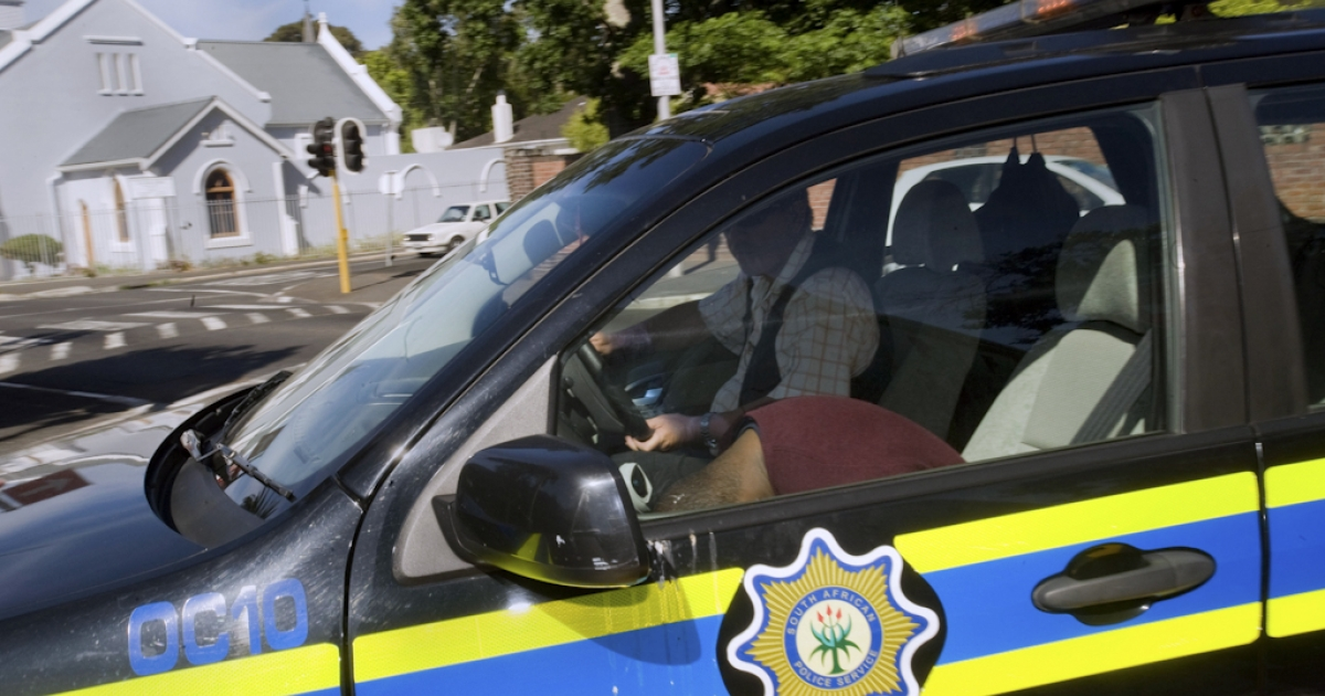 A member of the South African Police Services (SAPS) drives a suspect in a carjacking and murder case into a Cape Town court.</p>