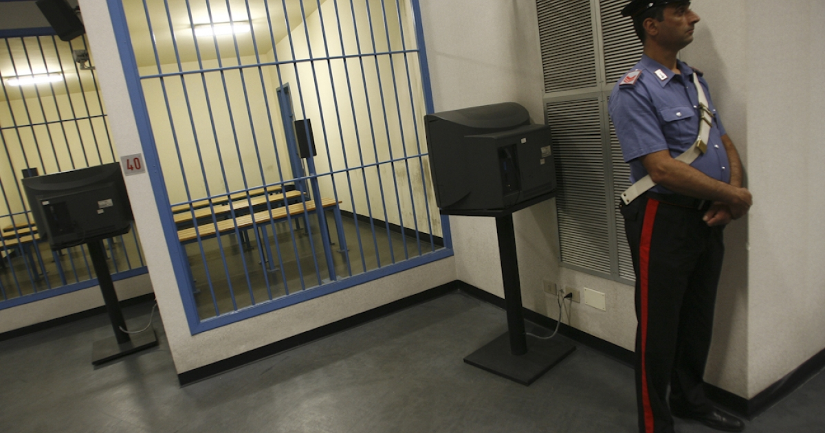 A member of the Italian Carbiniere stands by an empty cell in the Pagliarelli prison on June 29, 2010.</p>
