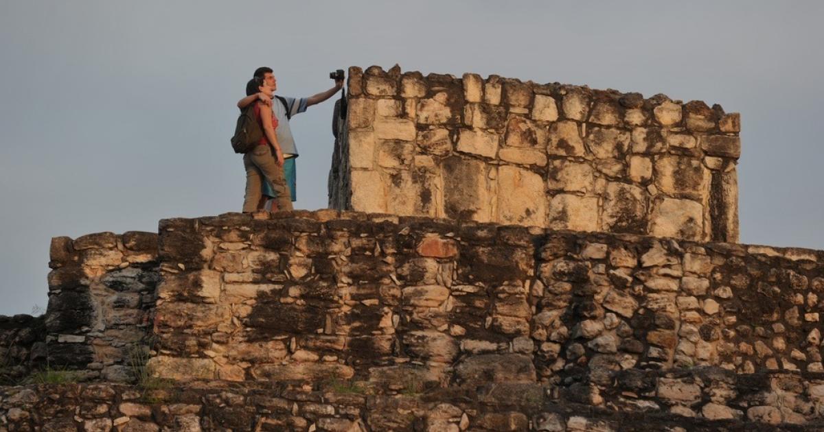 Tourists climb Mayan ruins in Mexico.</p>