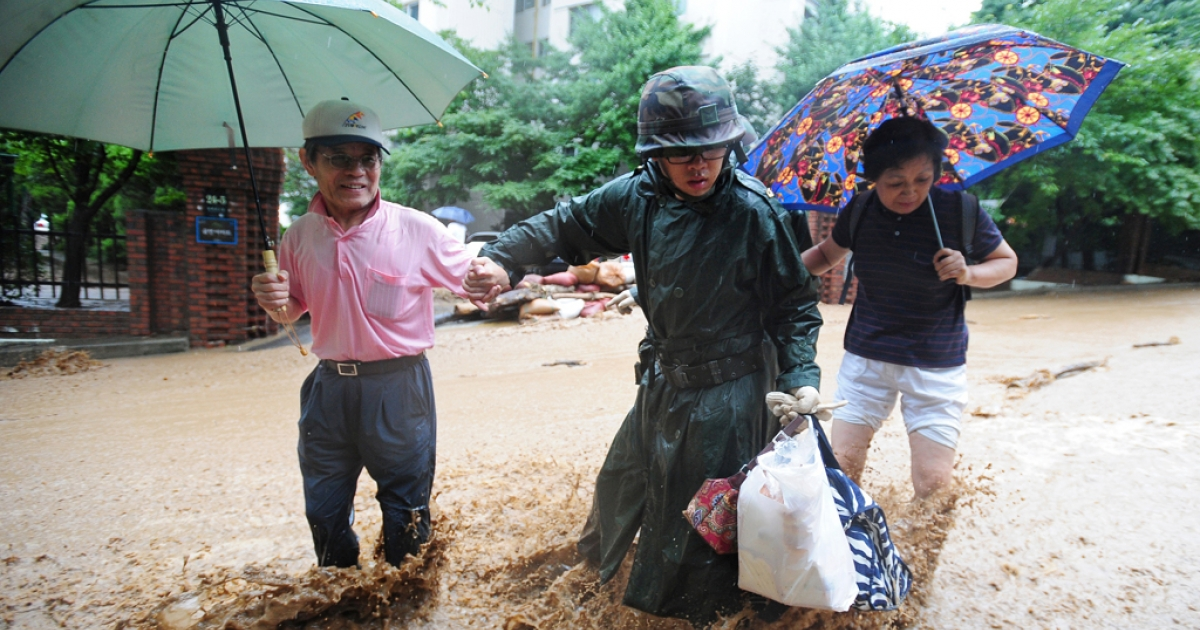 A South Korean soldier (C) escorts isolated residents through floodwaters and mud after a flood caused by heavy rains hit the area around an apartment complex in Seoul on July 28, 2011.</p>