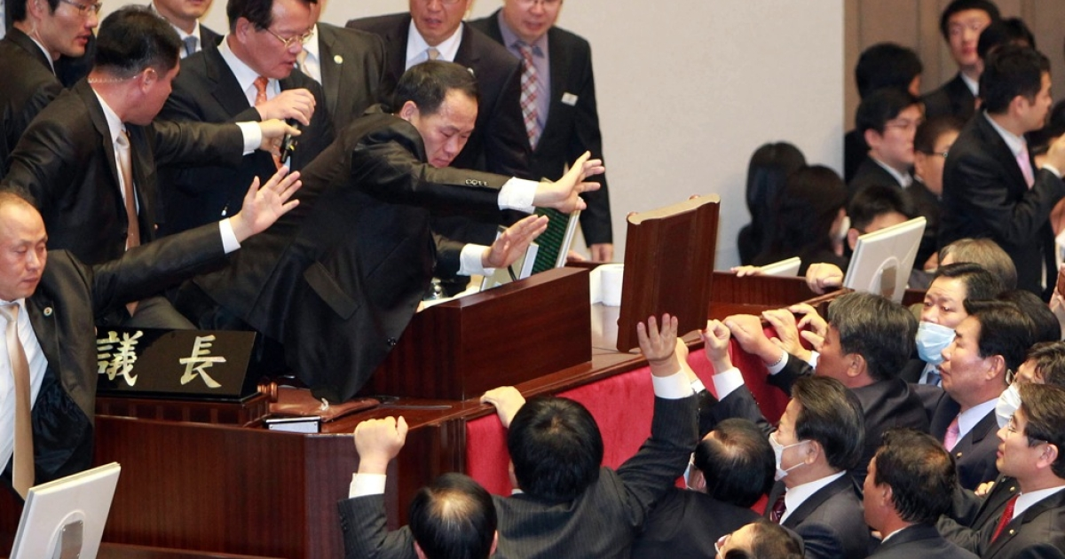 South Korea's opposition party lawmakers protest at the chairman's seat inside the National Assembly in Seoul, to try to stop the ruling Grand National Party's move to ratify a bill on a free trade agreement with the United States on November 22, 2011.</p>