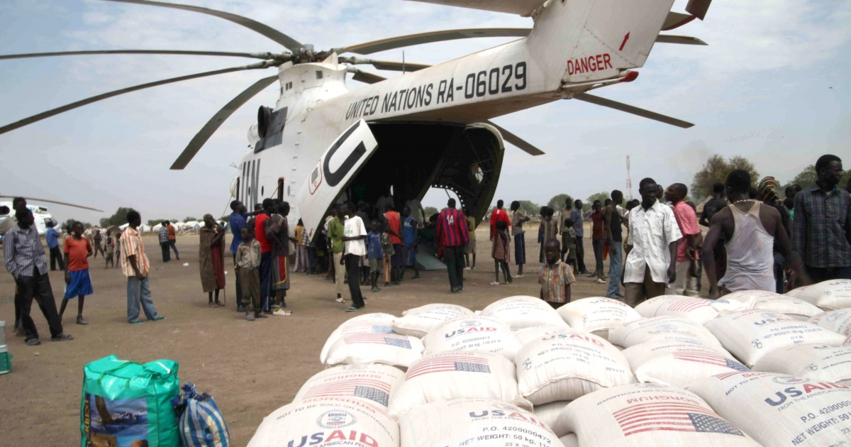 People stand around an helicotper provided by the UN Mission in South Sudan for the World Food Program in Pibor, South Sudan's Jonglei state, on January 12, 2012.</p>