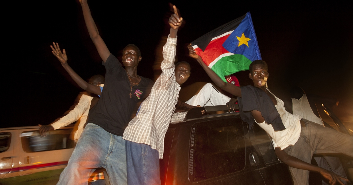 South Sudanese drive around waving the national flag celebrating into the night South Sudan's first anniversary of it's Independence day in Juba, South Sudan on July 9, 2012.</p>