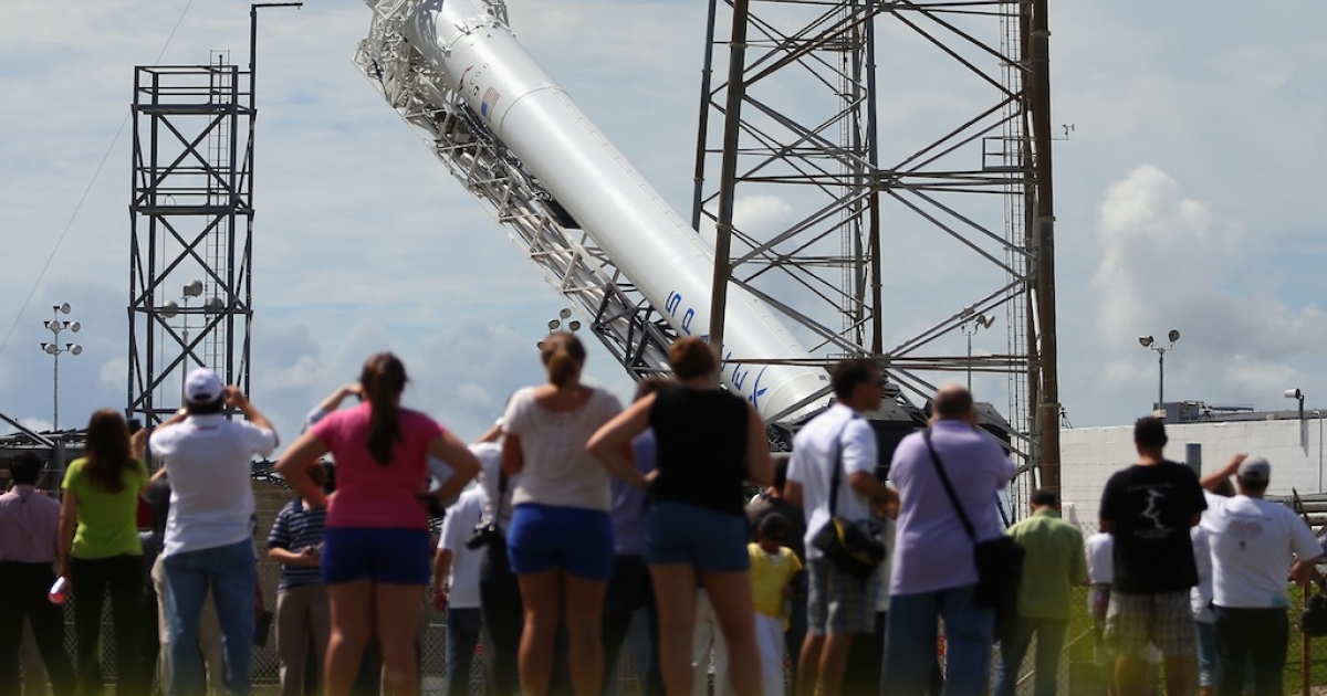 CAPE CANAVERAL, FL - OCTOBER 07: People watch as a SpaceX Falcon 9 rocket attached to the cargo-only capsule called Dragon is raised into launch position as it is prepared for a scheduled evening launch on October 7, 2012 in Cape Canaveral, Florida. The rocket will bring cargo to the International Space Station that consists of clothing, equipment and science experiments.</p>