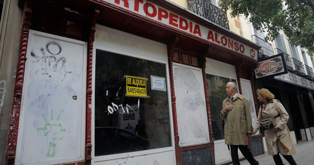A couple walk past a closed down orthopedic shop on November 10, 2011 in Madrid.</p>