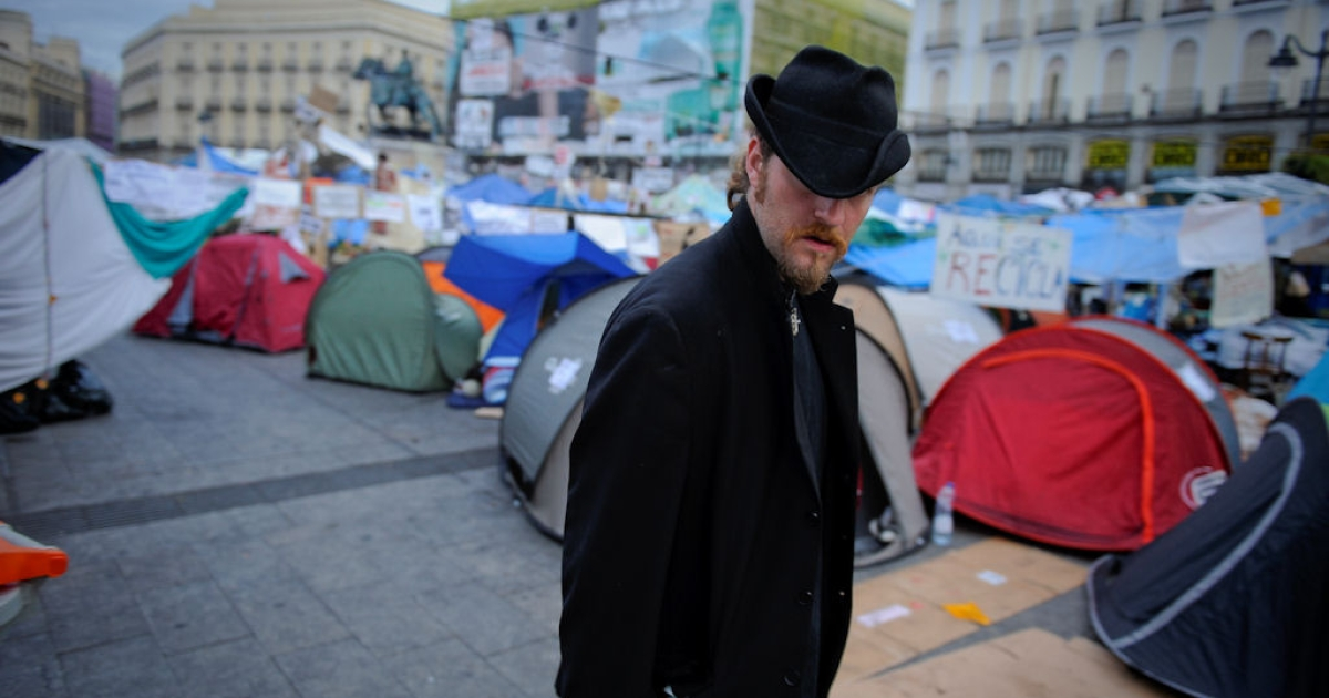 A man stands among tents as protesters camp at the Puerta del Sol square in Madrid on May 27, 2011.</p>