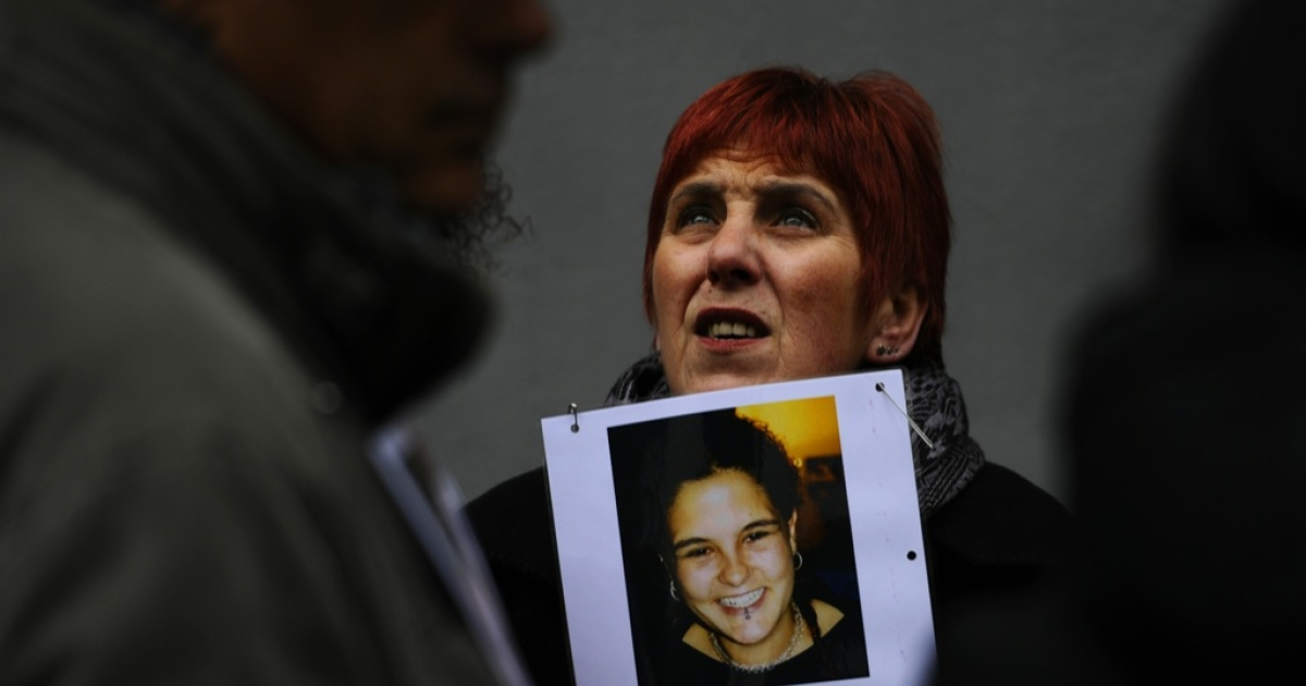 A woman holds a poster displaying a picture of a young girl and reading 'We are looking for her twin' during a demonstration against baby trafficking on Jan. 27, 2012 in Madrid.</p>