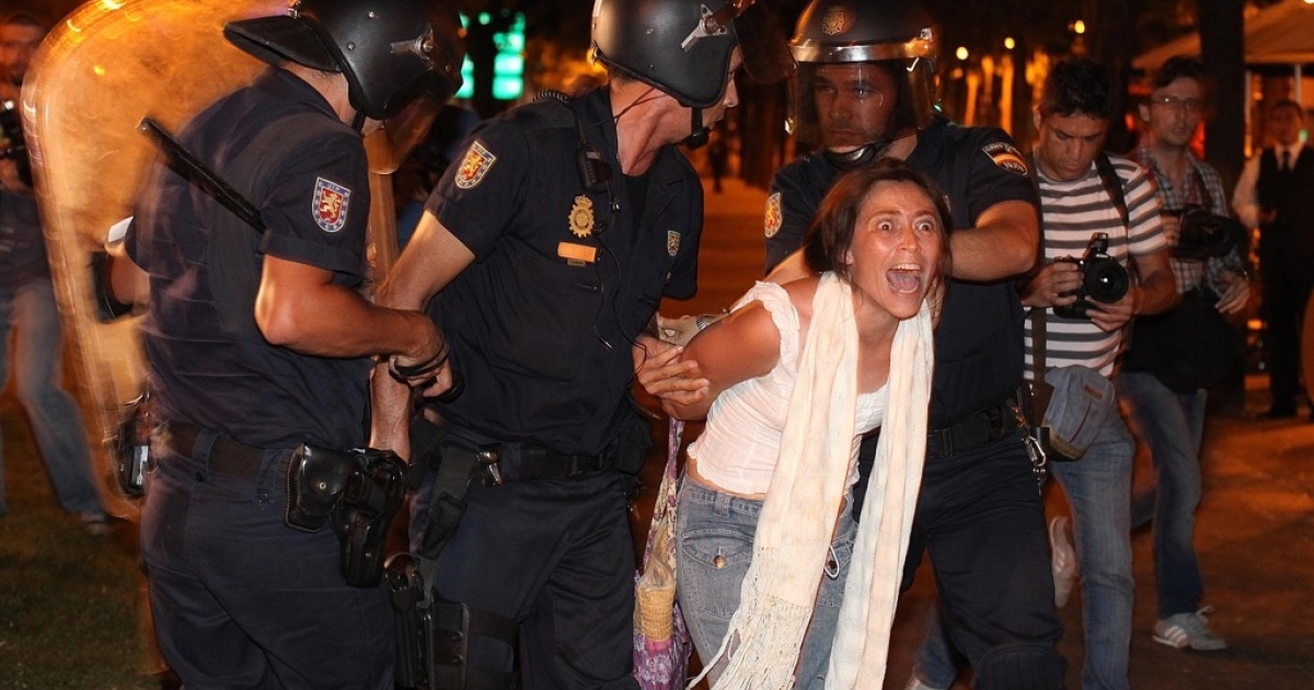 Spanish riot policemen arrest a woman on August 4, 2011 as they charged hundreds of