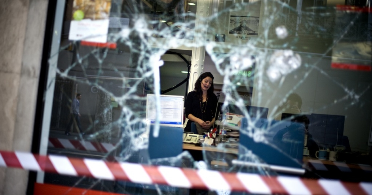 A Carslon Wagonlit Traves employee is seen through a broken window on March 30, 2012 in Barcelona, Spain. Protestors took to the street as the Spanish government prepared to approve a new austerity budget.</p>