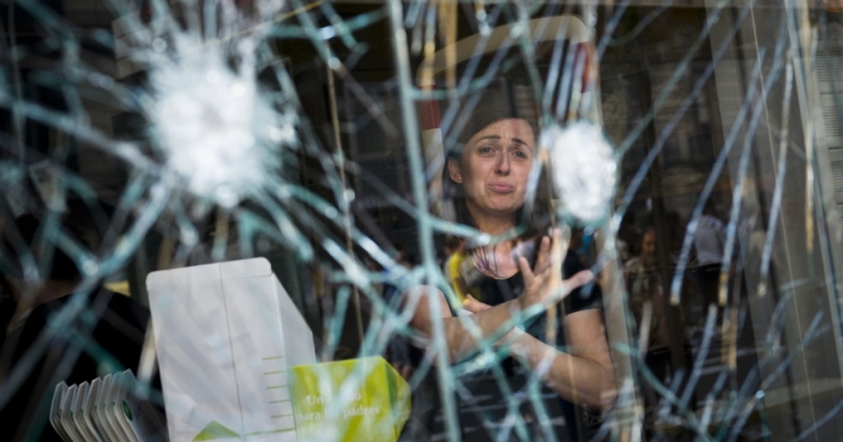 A woman cries behind the smashed window of her shop during heavy clashes with riot police during a 24-hour strike on March 29, 2012 in Barcelona, Spain.</p>