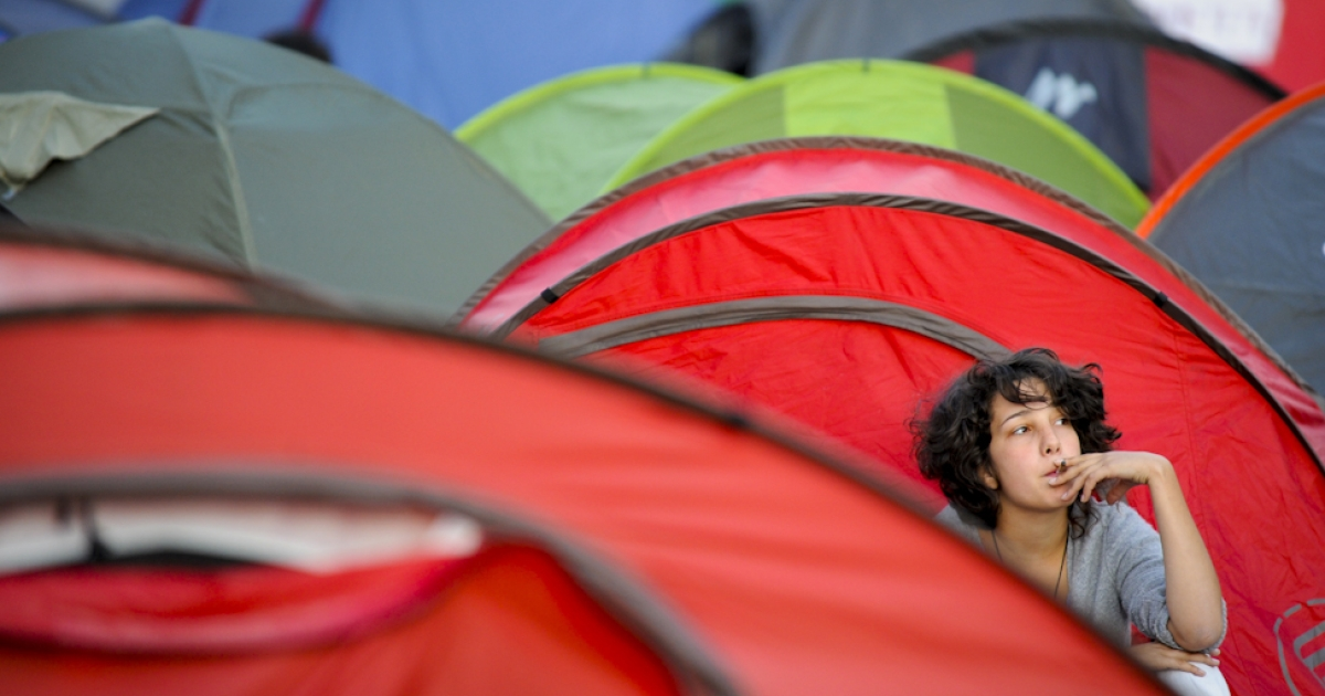 A demonstrator smokes a cigarette outside her tent as protesters occupy the Puerta del Sol square in Madrid on May 24, 2011 during a demonstration against Spain's economic crisis and its sky-high jobless rate. Protesters describe themselves as the 'indignant', and are known variously as 'M-15' in reference to their demonstration's birth date, 'Spanish Revolution' and 'Real Democracy Now'. Spain's ruling Socialists sustained spectacular local election losses on May 22 as protesters vented outrage over the highest jobless rate in the industrialized world.</p>