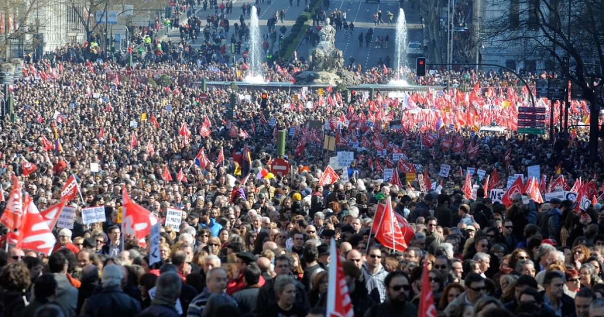 MADRID, SPAIN - FEBRUARY 19:  Protesters pass Plaza Cibeles square during a march by thousands of demonstrators against the government's new labour reform law on February 19, 2012 in Madrid, Spain. According to reports, the reforms have prompted marches in 57 cities, as the government seeks to revive the ailing economy and tackle the jobless rate of nearly 23 percent, the highest in the Eurozone.</p>