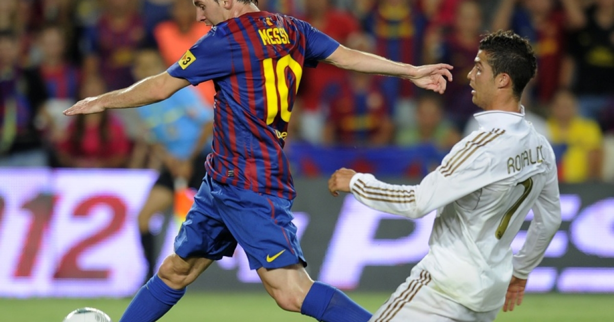 Barcelona's Argentinian forward Lionel Messi (L) scores a goal as he vies with Real Madrid's Portuguese forward Cristiano Ronaldo during the second leg of the Spanish Supercup football match FC Barcelona vs Real Madrid CF on August 17, 2011 at the Camp Nou stadium in Barcelona.</p>