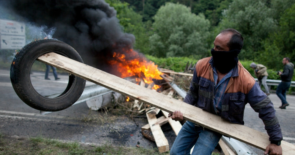 A Spanish miner holds a burning tire next to a barricade near Santiago mine.</p>