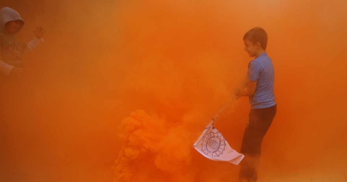 Children wave flags through smoke thrown by firemen and policemen during a demonstration of public service workers against government's spending cuts in Sevilla on September 29, 2012. Spain's government said it would freeze public sector pay, which has not risen since it was cut by five percent in 2010 and which suffered an effective seven-percent fall this year with the cutting of the end-of-year bonus.</p>
