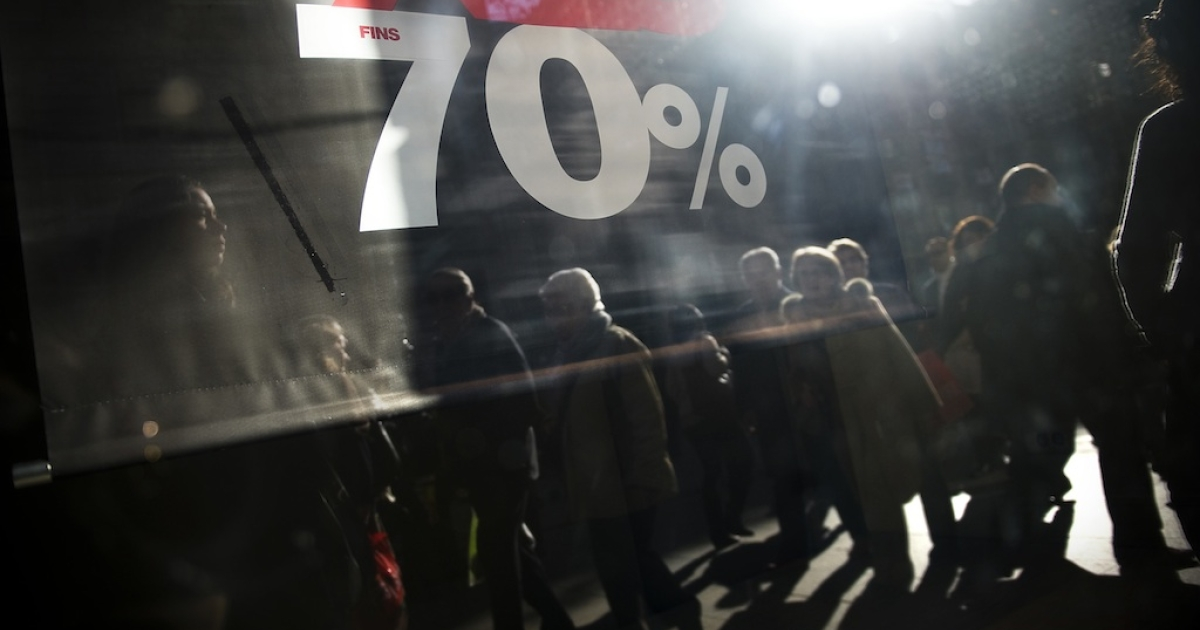 Customers are seen reflected in a display window of a store advertising sales on the first day of the winter sales in Spain on January 7, 2012 in Barcelona, Spain.</p>