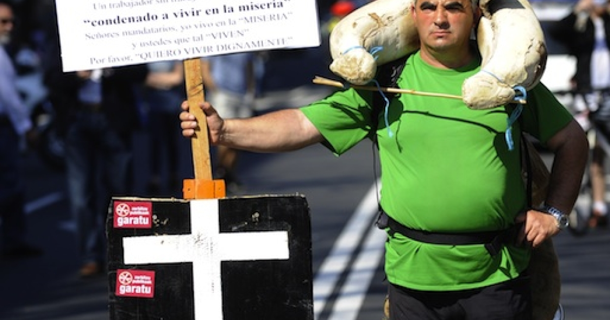 An unemployed man holds a placard reading 'Thanks for my future' as he takes part in a demonstration in the northern Spanish Basque city of Bilbao during a national strike on March 29, 2012.</p>