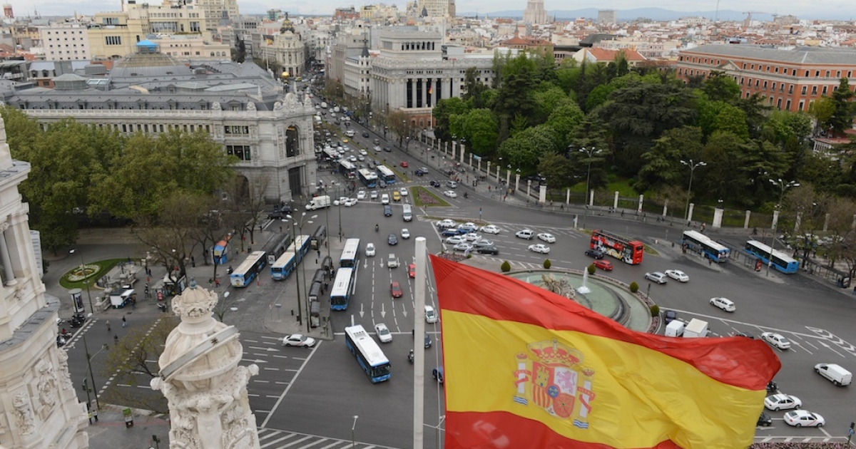 The Spanish flag at the Plaza de Cibeles in Madrid.</p>