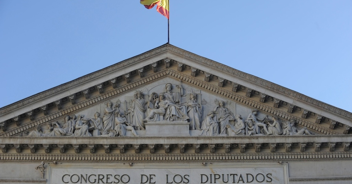 The national flag flies over the Spanish parliament in Madrid.</p>