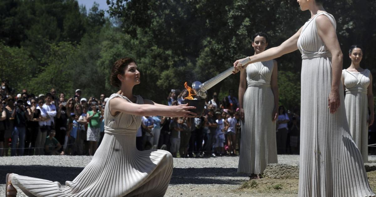 Ino Menegaki, right, passes the Olympic flame on May 9, 2012, during the torch lighting ceremony in Olympia, the sanctuary where the Olympic Games were born in 776 B.C.</p>