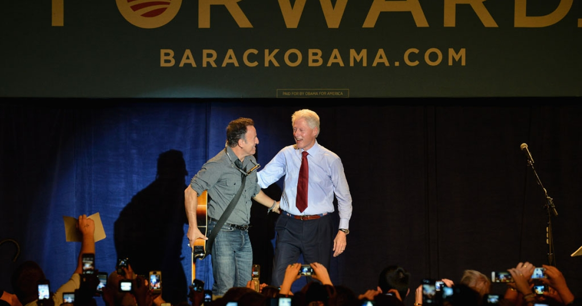 Former US President Bill Clinton greets Bruce Springsteen on stage during the