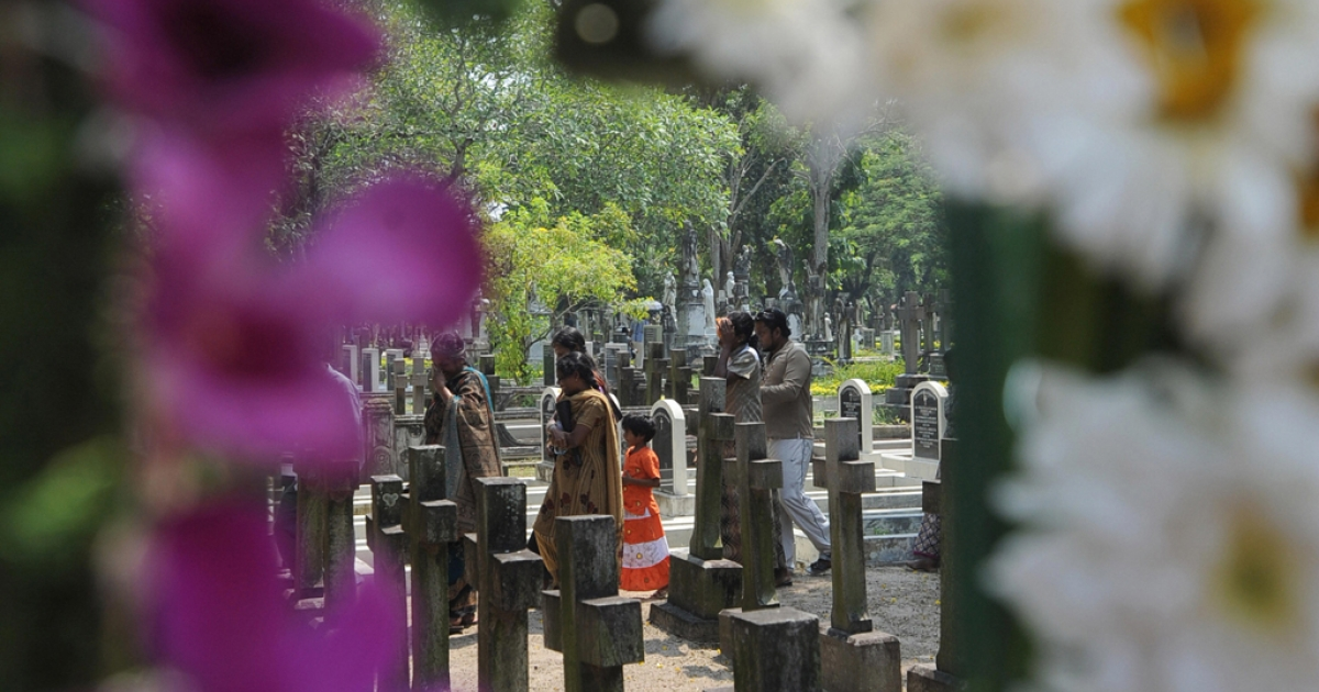 Relatives leave after placing flowers on the grave of a loved one on All Souls Day at the main cemetery in the Sri Lankan capital of Colombo on Nov. 2, 2008. AFP PHOTO/Ishara S. KODIKARA (Photo credit should read Ishara S. KODIKARA/AFP/Getty Images)</p>