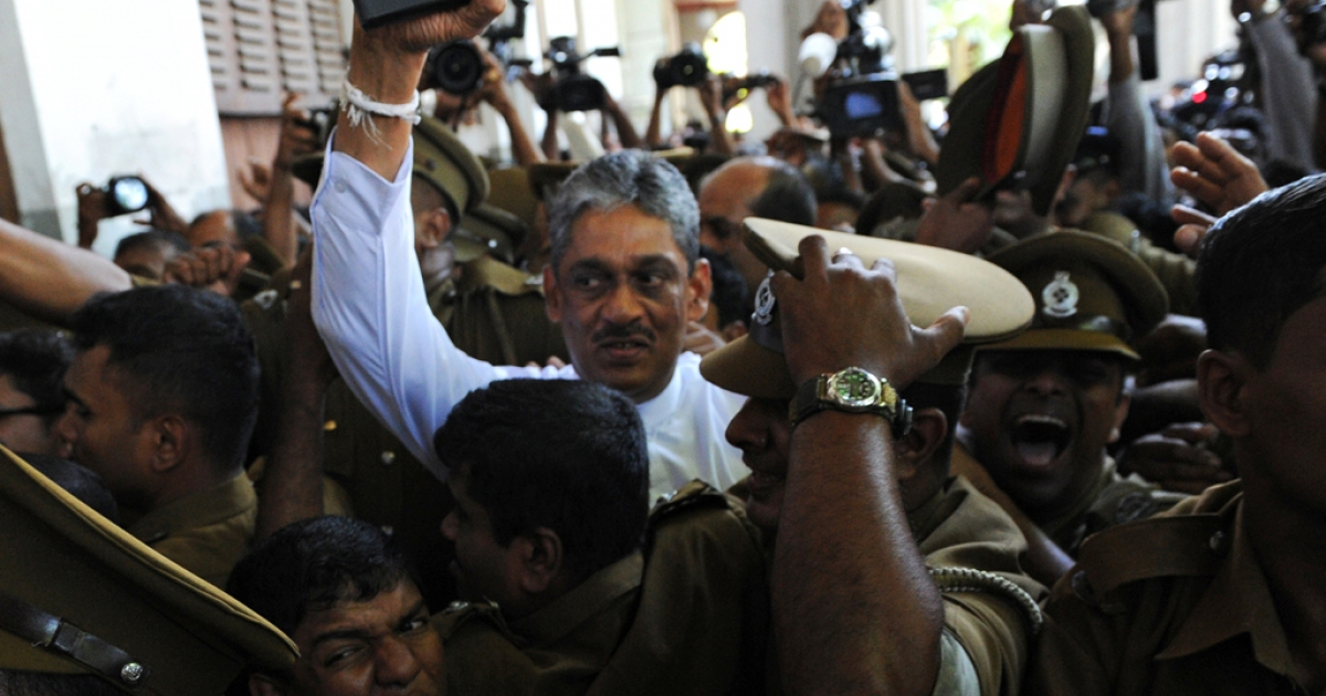 Sri Lanka's former army chief Sarath Fonseka is escorted by police as he arrives at the Colombo High Court in Colombo on November 18, 2011.</p>