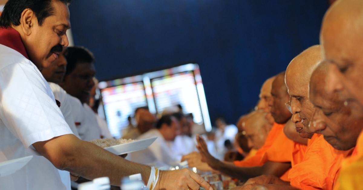Sri Lankan President Mahinda Rajapakse serves food to a Buddhist monk in the capital Colombo. The Sri Lanka health ministry will release guidelines in December for devotees offering food donations to monks, over concerns of the monks' weight and health.</p>