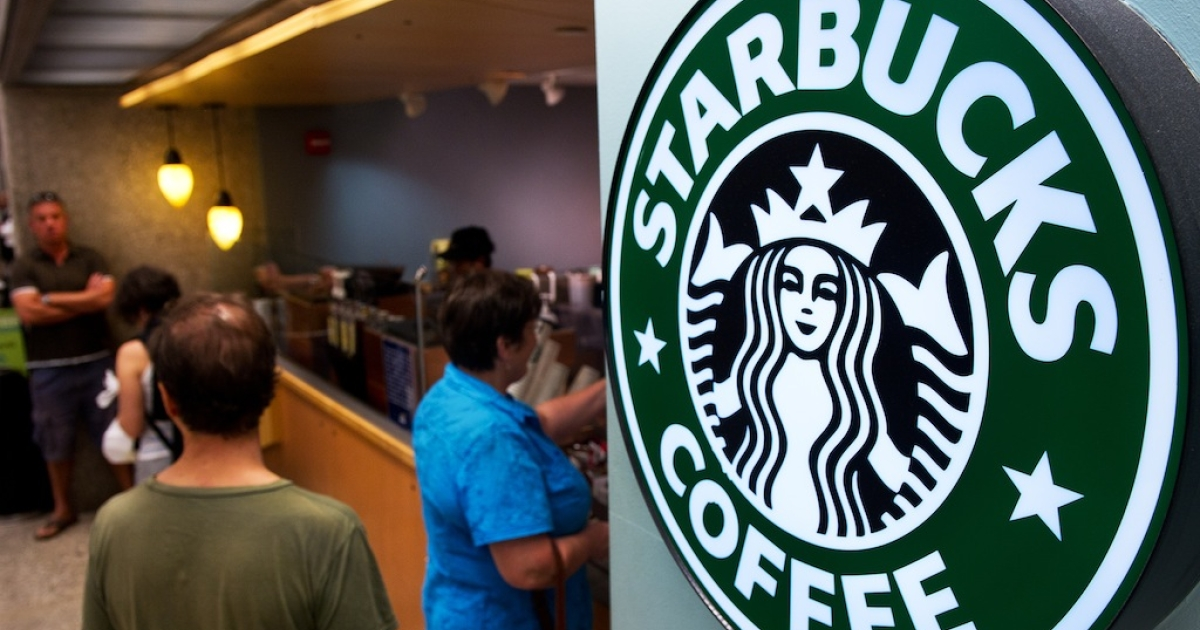 Customers queue for coffee at a Starbucks inside the Dulles International Airport complex on August 30, 2011 in Dulles, Virginia, near Washington, DC.</p>
