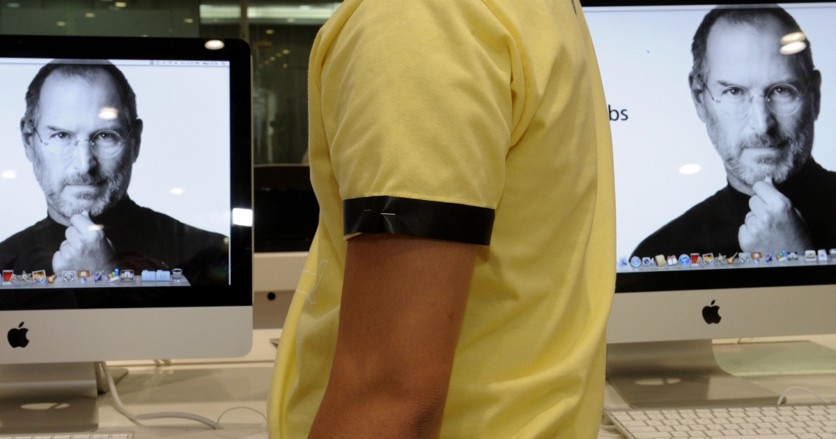 A sales clerk at an Apple store in Manila wears a black arm band to mourn the death of Apple co-founder and chairman Steve Jobs.</p>