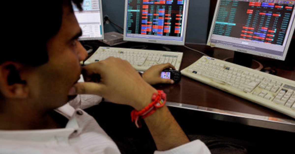 An Indian stock dealer watches share prices on his terminal at a brokerage house in Mumbai on September 26,</p>