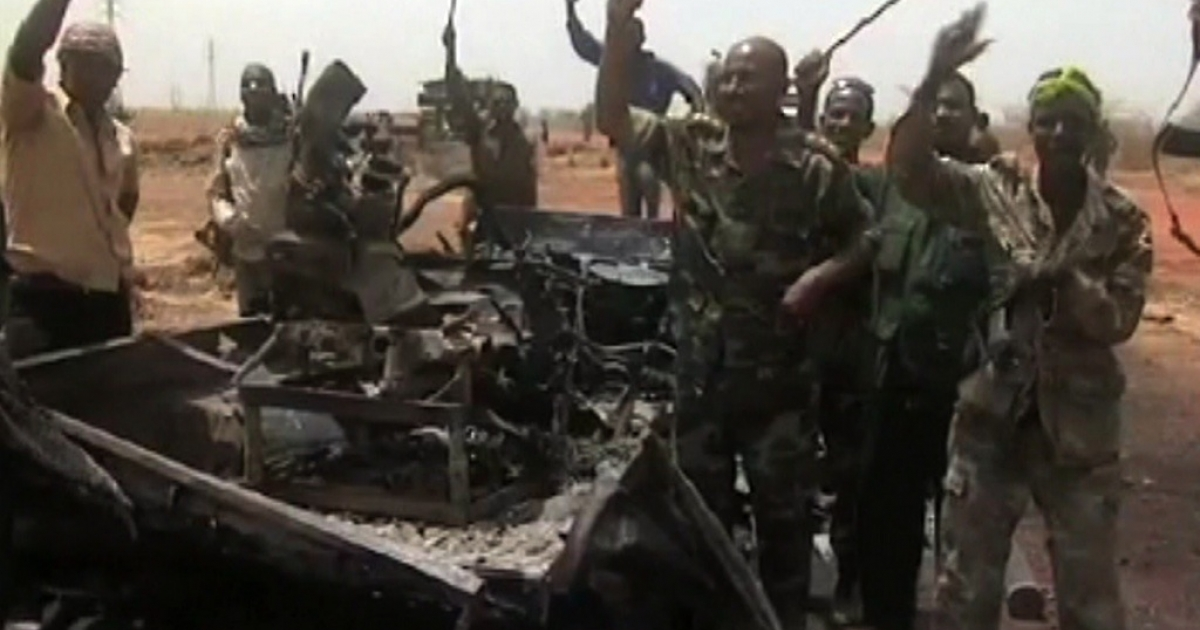 An image grab taken from footage obtained by AFP shows Sudanese troops celebrating next to a burned military vehicle on March 29, 2012, one day after recapturing Sudan's southern oil center of Heglig following fighting with South Sudanese forces along the border. Southern troops have once again seized the Heglig oilfields, parts of which are claimed by both countries.</p>
