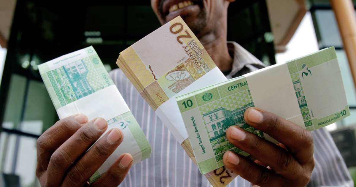 A Sudanese man shows freshly-minted notes of the new Sudanese pound in Khartoum.</p>