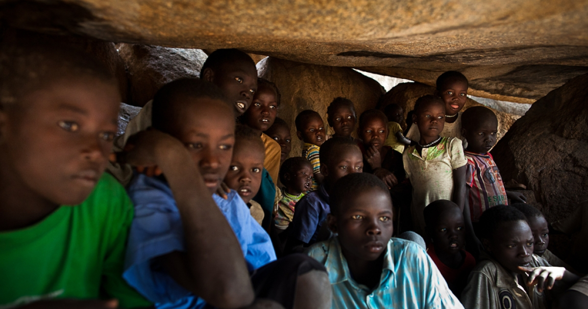 Nuba children take shelter in caves as a Sudan Armed Forces Antonov bomber passes overhead on July 13, 2011.</p>