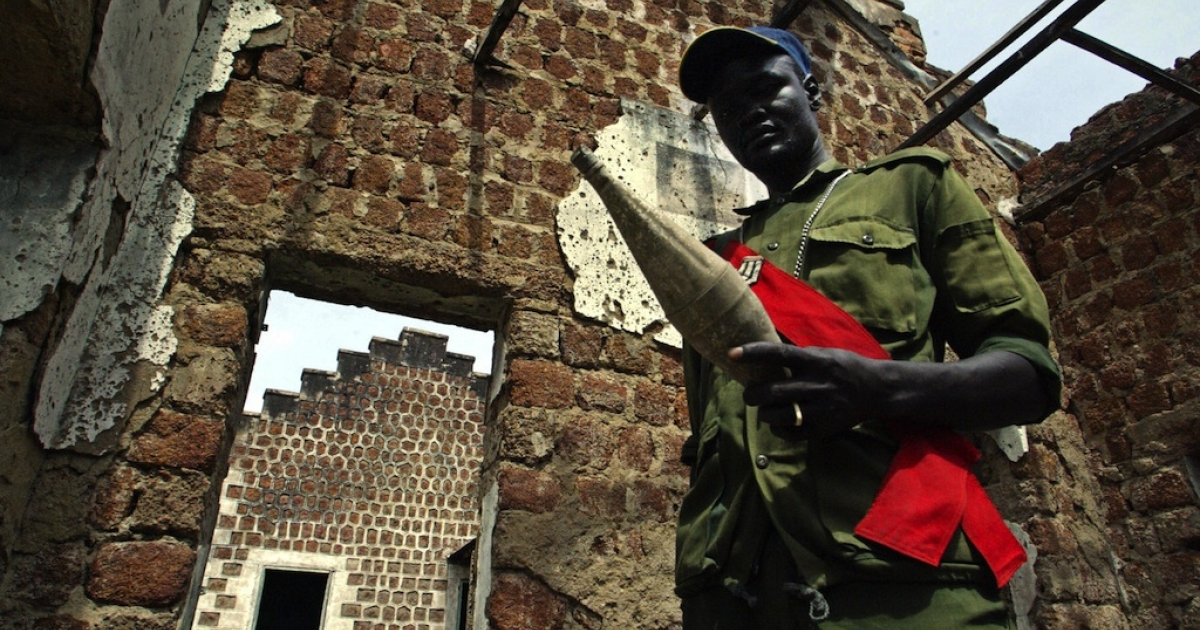 A soldier of the Sudan People's Liberation Army (SPLA) inspects an unused RPG missile in the ruins of a bombed-out building in the southern town of Rumbek on Jan. 21, 2005.</p>