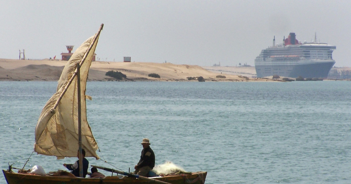 A traditional fishing boat navigates off the Egyptian port town of Ismailia, 80 miles northeast of Cairo, on March 28, 2009, as the luxury ocean liner Queen Mary II (R) transits northbound through the Suez Canal on its way to the Mediterranean Sea.</p>