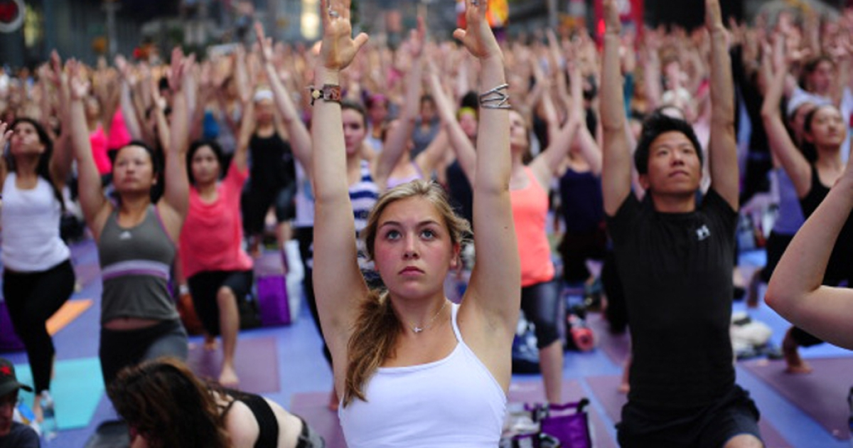 Participants take part in a mass yoga class to mark the summer solstice in New York City's Times Square on June 20, 2012.</p>