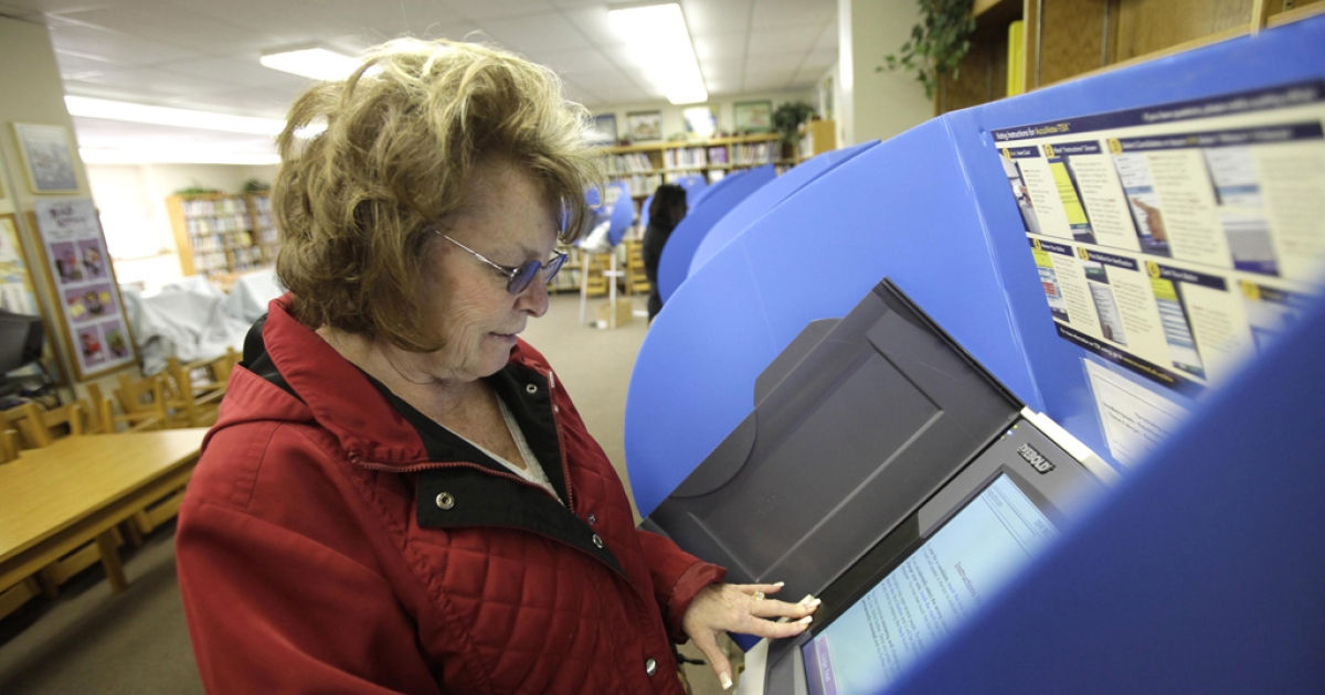 Barbara Bovee casting her ballot at a polling station setup on