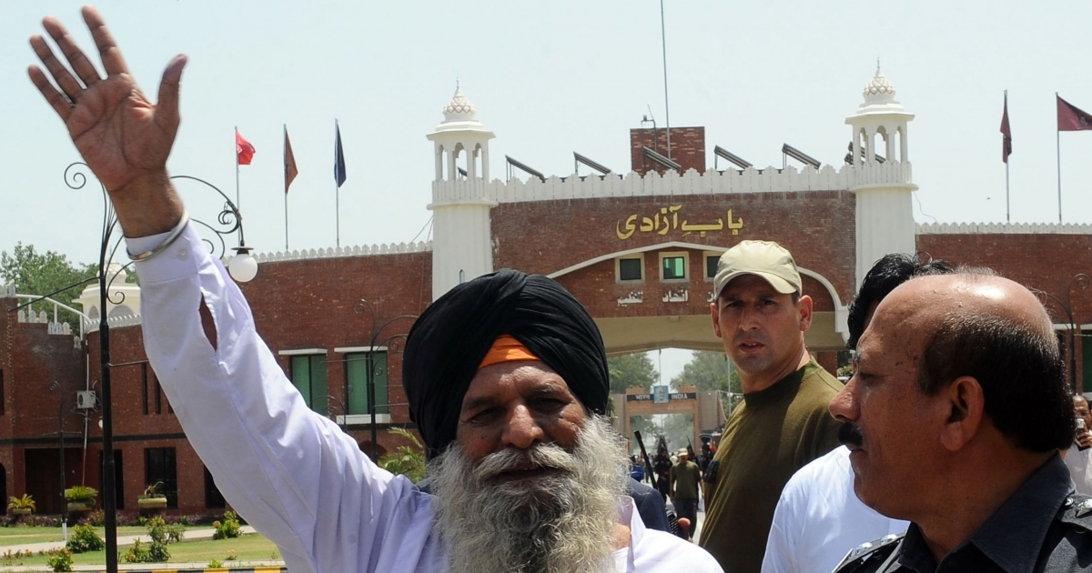 Released Indian prisoner Surjeet Singh, escorted by Pakistani security officials, waves before leaving Pakistan for India at the Wagah border on June 28, 2012.</p>