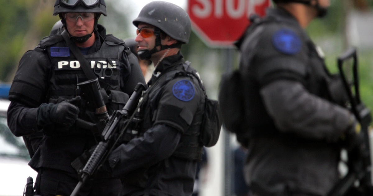 Miami SWAT team members stand in front of a home that was raided Sept. 27, 2006 in Miami, Florida. The raid was part of an ongoing crack-down in a neighborhood affected by violence.</p>