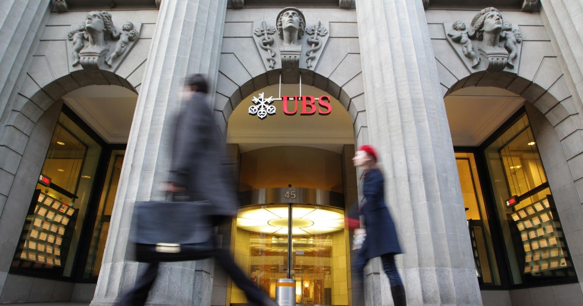 People walk on February 8, 2011 in front of the headquarters of Swiss bank UBS in Zurich. .</p>