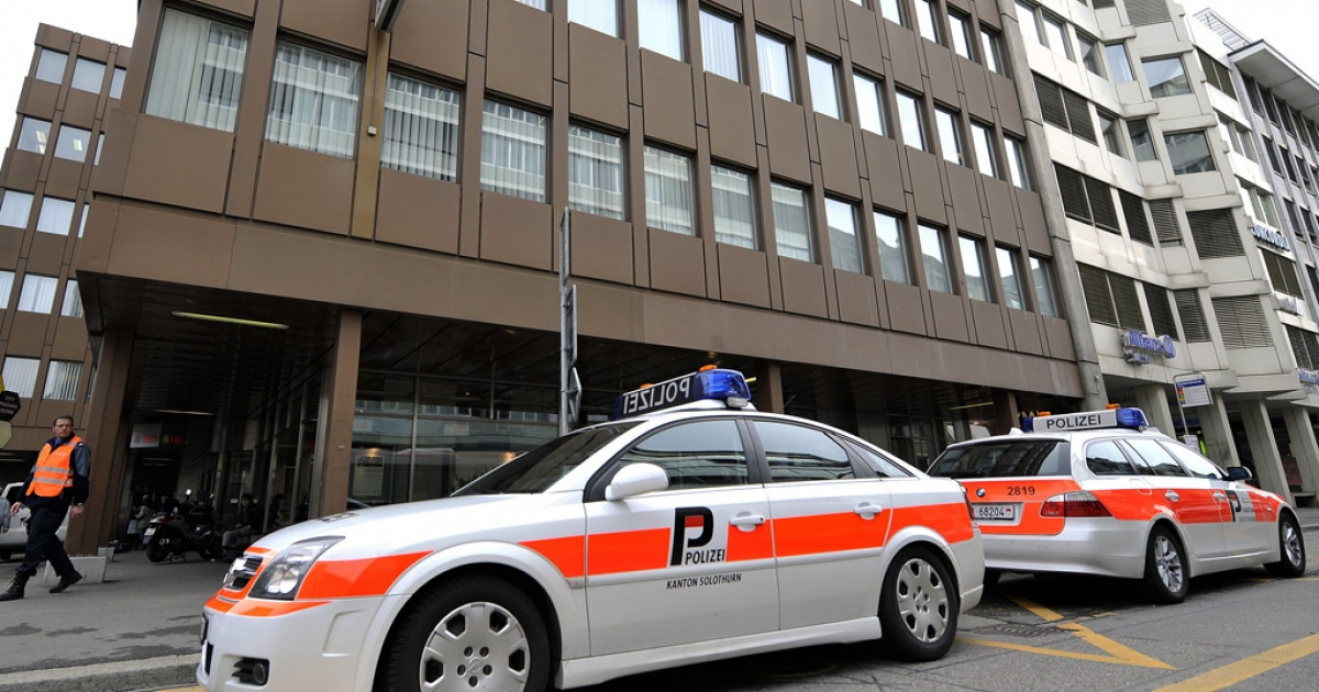 Police cars are seen next to the building housing the Swiss nuclear power industry association, on March 31, 2011 in Olten.</p>