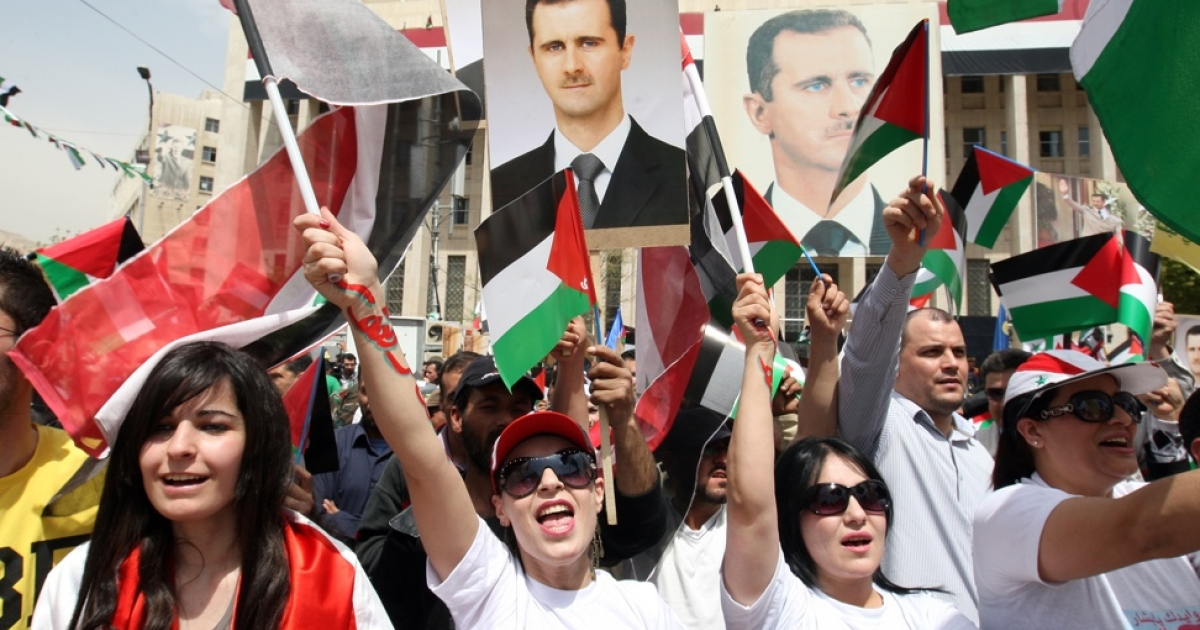 Supporters of President Bashar al-Assad (portrait) wave Syrian Baath Party flags and the Syrian flag during a march in Damascus on April 7, 2012.</p>