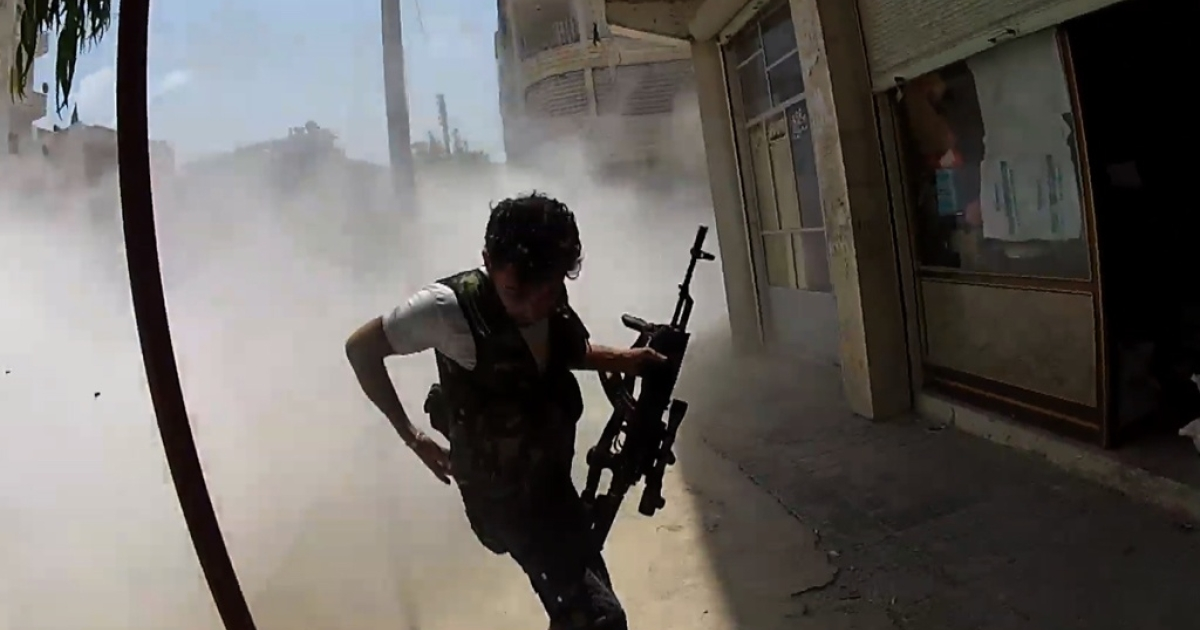 A rebel runs from government fire in the city of Ariha, northern Syria.</p>