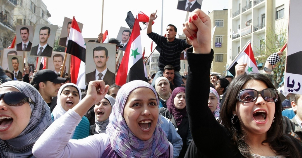 Syrians chant slogans and hold portraits of President Bashar al-Assad during a rally to show support for their leader in Damascus on March 29, 2011.</p>