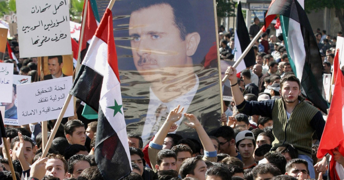 Syrians, some carrying portraits of their president Bashar al-Assad, rally in support of the regime.</p>